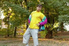 Young handsome caucasian man with bright freaky sportswear 70s style stands at a morning park. Stick in the mouth, golden glasses,. Earring and ring royalty free stock photos