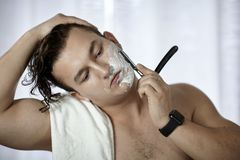Young handsome caucasian man with electronic watch on wrist shaves with straight razor vintage style of old barbership. Thoughtf. Ul serious look, towel on the stock image