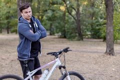Young handsome caucasian man stands hands crossed with bicycle frowning and serious. White wireless earphones, casual sportswear. royalty free stock images