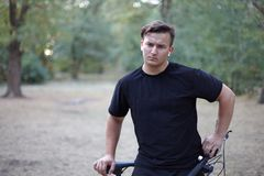 Young handsome caucasian man stands with his bicycle at the middle of park or forest. Very serious and thoughful, frowns. White ea stock photo