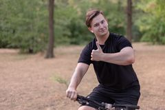 Young handsome caucasian man thumbs up bicycling at the park stock photography