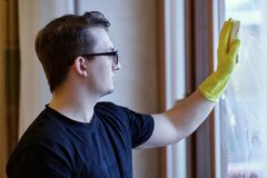 Young handsome caucasian man washes the window with sponge. Dark curly hair, glasses, smart look, little sad expression. Housekeep stock images