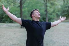 Young handsome caucasian man widely stretches out his hands arms at the park background. Wears casual black t-shirt, white earphones, earring, ring. Outdoor stock image
