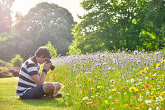 Young handsome caucasian photographer in botanic gardens. Royalty Free Stock Photos