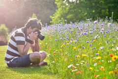 Young handsome caucasian photographer in botanic gardens. Stock Photo
