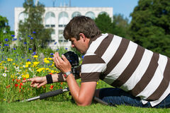 Young handsome caucasian photographer/videographer in botanic gardens. Royalty Free Stock Images