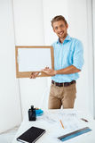 Young handsome cheerful smiling businessman standing at table holding wooden clipboard with white sheet pointing on it Stock Image