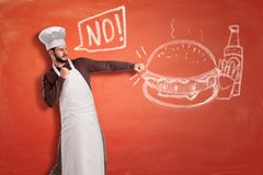 A young handsome chef saying `No` and hitting with clenched fists a chalk drawing of a hamburger, French fries and a. Ketchup bottle. Say no to junk food. Start royalty free stock photos