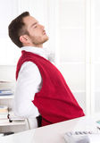 Young handsome clerk with backache at office. Young attractive businessman with rheumatism at office Stock Image