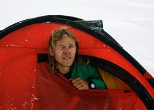 Mountaineer in a red tent on snow in the mountains of Pamir. A young handsome climber looks out of a red tent. Pamir mountains, climbing Lenin Peak Royalty Free Stock Image