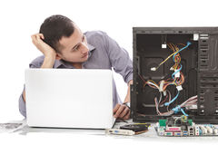 Young handsome computer specialist look confuse repairing comput Stock Image