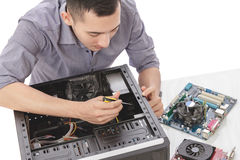 Young handsome computer specialist repairing computer with full Royalty Free Stock Photography