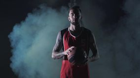 Portrait bearded young brutal confident basketball player stand with a ball in the clouds of smoke on black background. stock footage