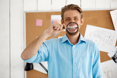Young handsome confident funny businessman standing over cork board holding magnifier. Looking in camera. White modern Stock Photo