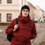 Young handsome confident man in a black knitted hat in a trendy red long jacket with a black backpack is standing outdoors. Near vintage buildings. Nice model royalty free stock images