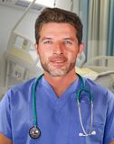 Young handsome and confident medicine doctor posing cheerful on blue scrubs and stethoscope on his neck smiling happy isolated on stock image