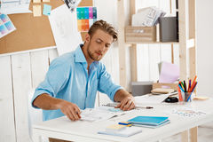Young handsome confident pensive businessman working sitting at table looking through papers. White modern office Stock Photo