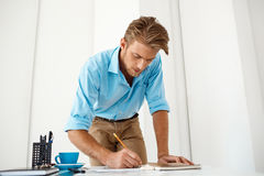 Young handsome confident pensive businessman working standing at table writing in notepad. White modern office interior Stock Images