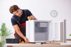 Young handsome contractor repairing fridge royalty free stock image
