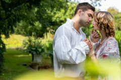 Young handsome couple dressed in vintage costume standing on embankment by river and under trees, kissing.