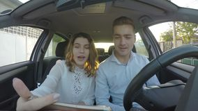 Young handsome couple having conversation trough video call in the car on smart phone - stock video footage
