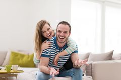 Young handsome couple hugging on the sofa Stock Photo