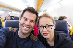Young handsome couple taking a selfie on commercial airplane. Stock Image