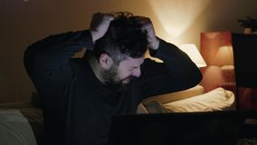 A bearded man, an employee goes crazy, loses his temper and shouts loudly in front of the monitor at his workplace. Young handsome crazy man working late in stock footage