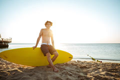 Young handsome curly resting while sitting on the surfboard. At the beach Stock Images
