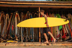 Young handsome curly surfer holding surf board. While standing at the shack outdoors Royalty Free Stock Images