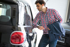 Young handsome customer in car showroom Royalty Free Stock Photography