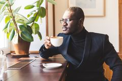 Young handsome dark-skinned businessman drinks coffee in a cafe. stock image