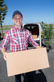 Young handsome delivery man standing near car Stock Photo