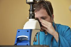 Young doctor researching on a microscope Stock Images