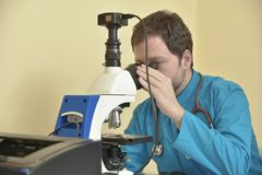 Young doctor researching on a microscope Stock Image