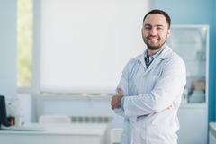 Young handsome doctor indoors at hospital office Stock Photos