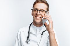 Young and handsome doctor talking on the phone with patients, Intern student with folder in hand, white background, for advertisin royalty free stock image
