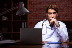 The young handsome doctor working night time at the hospital royalty free stock image