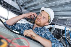 Young handsome electrician on phone Royalty Free Stock Photo