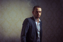 Young handsome and elegant man posing isolated over vintage background. Royalty Free Stock Photos