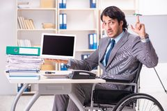 The young handsome employee in wheelchair at the office. Young handsome employee in wheelchair at the office royalty free stock photos