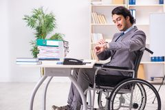 The young handsome employee in wheelchair at the office. Young handsome employee in wheelchair at the office stock images