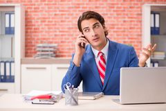 The young handsome employee working in the office royalty free stock photos