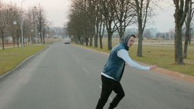 A young, handsome, energetic guy in black trousers and a blue hooded vest performing a hip-hop dance on the roadway with. Steadicam shot of a young, handsome stock video