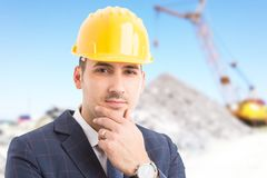 Young handsome engineer on construction site. Young handsome engineer or architect wearing helmet and thinking as professional inspecting concept on construction Stock Image