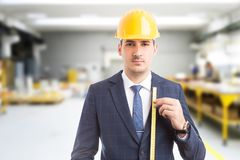 Engineer holding measure tape in factory. Young handsome engineer holding measure tape and wearing helmet as building job concept on factory background Stock Images