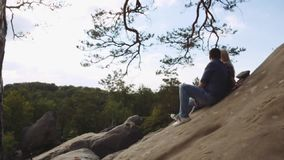 Young handsome European guy in a casual jeans wear and beautiful elegant blonde girl. A couple sitting on the top of stock video footage
