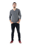 Young handsome fashion model in gray shirt with hands in pockets looking at camera. Full body length portrait isolated over white studio background Royalty Free Stock Images