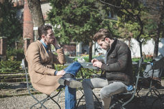 Young handsome fashion model using tablet man. Two young handsome fashion model using tablet men outdoors Stock Photo
