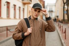 Young handsome fashionable man in a stylish vintage coat. With a black bag adjusts his cap on the street Stock Photo